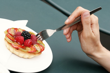 poking: A hand holding a fork poking a fruit pie Stock Photo