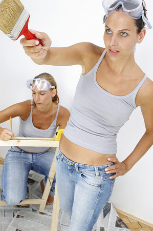 A woman is measuring a wood while her friend is painting the wall photo