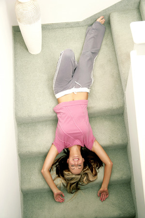 highlighted hair: A lady lying upside down on the stairs