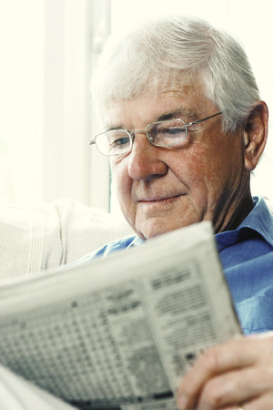bespectacled man: An old bespectacled man reading newspaper Stock Photo