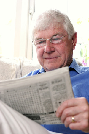 bespectacled man: A bespectacled old man sitting on the couch reading newspaper