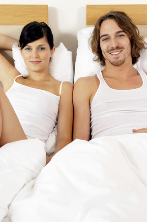A couple sitting together on two single beds photo