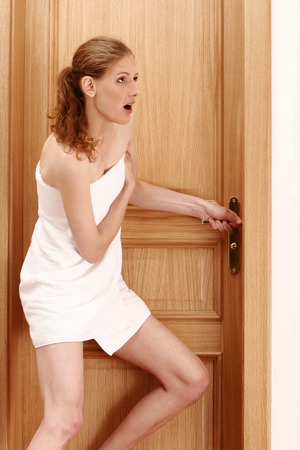 locked: A lady wrapped in towel trying to open the door