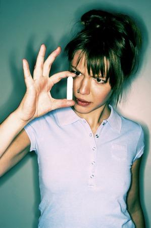 tampon: Una mujer con estudios nariz sostiene un tamp�n Foto de archivo