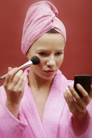 towel wrapped: A lady in pink bathrobe and towel wrapped hair brushing some blusher on her cheek