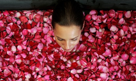 spoiling: Top view of a woman bathing in a bathtub of flower petals