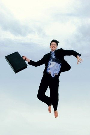 A man in business suit holding a briefcase jumping high up in the sky photo