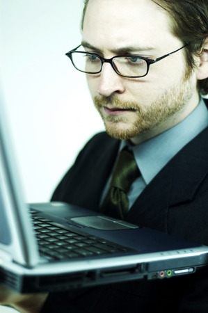 bespectacled man: A bespectacled man holding a laptop near to his body Stock Photo