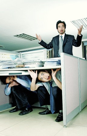 men at work: Two men hiding under a table while another man searching for them