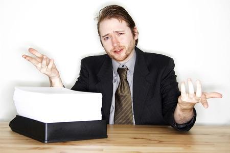 restlessness: A man wondering how he is going to handle the stack of paperwork in front of him