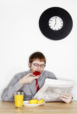 bespectacled man: A bespectacled man in working attire reading newspaper while having his breakfast