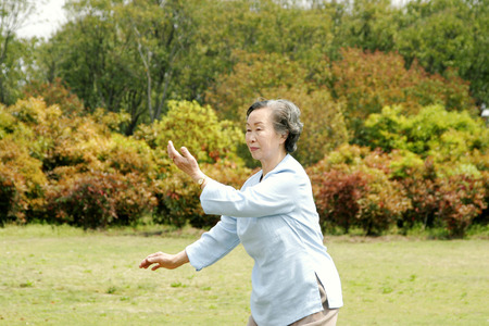 An old woman practicing tai chi in the park