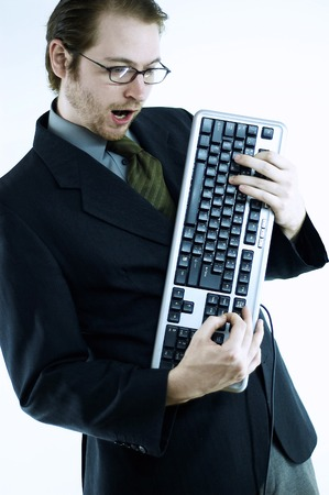 bespectacled man: A bespectacled man holding a computer keyboard like he is playing a guitar