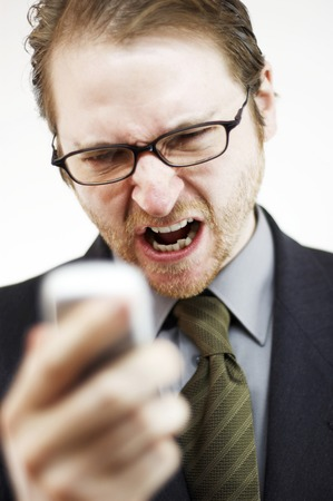 bespectacled man: A bespectacled man looking angry reading the messages on his hand phone