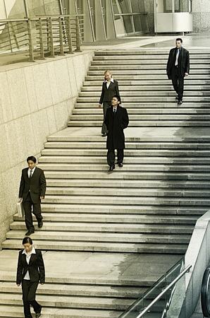 bajando escaleras: Las personas que trabajan en traje de la oficina caminando por las escaleras