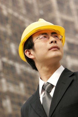 bespectacled man: A bespectacled man in business suit and protection helmet standing at the construction site