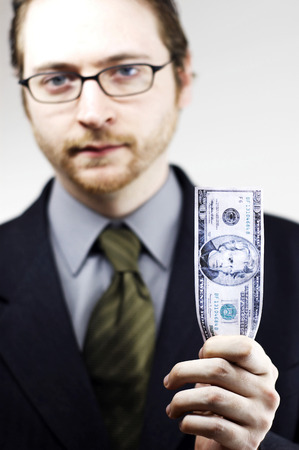 bespectacled man: A bespectacled man in business suit holding a banknote