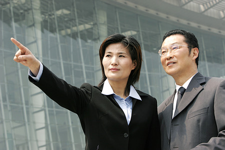 bespectacled man: A woman in business suit showing something to a bespectacled man Stock Photo