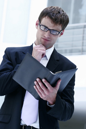 figuring: A with black rimmed spectacles reading his organizer