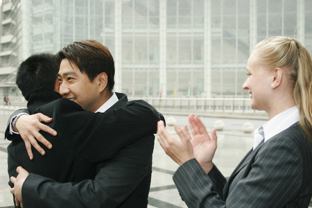 An Asian man hugging his friend while a lady clapping her hands photo