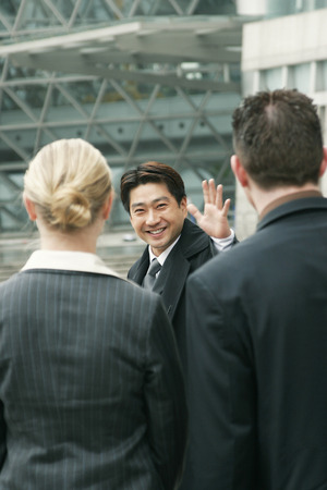 An Asian man waving goodbye to a man and woman photo