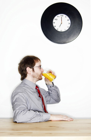 bespectacled man: Side shot of a bespectacled man drinking a glass of orange juice for his breakfast