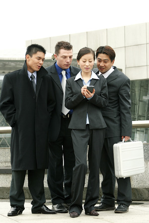 palmtop: Three guys in business suits watching as a lady tapping on her palmtop Stock Photo