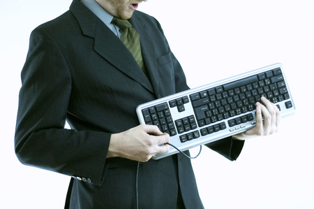 A man in business suit holding a computer keyboard like he is playing a guitar