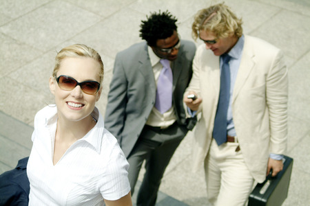 A woman with sunglass walking up the stairs with two men walking behind photo