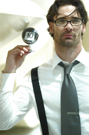 bespectacled man: A bespectacled man holding up a number