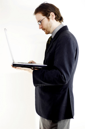 bespectacled man: Side shot of a bespectacled man in business suit placing a laptop on his palm