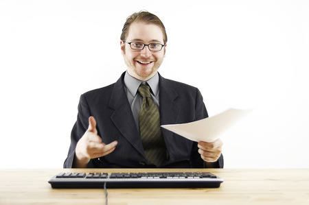 desirous: A bespectacled man in business suit looking happy sitting at his desk in the office Stock Photo