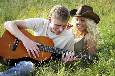 A man lying on the grass playing guitar for his girlfriend