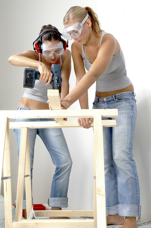 deafening: A woman helping her friend to hold the wood as she is drilling