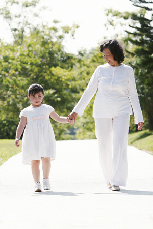 An old lady and her granddaughter walking together holding hands in the park photo