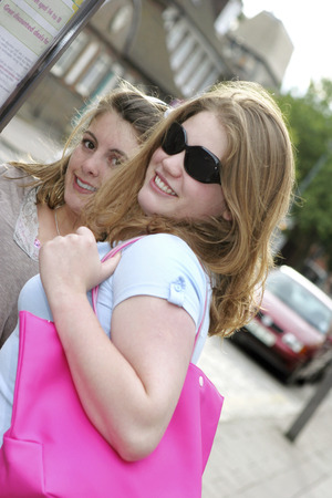 tote: A lady with sunglasses and carrying a pink tote bag walking with her friend Stock Photo