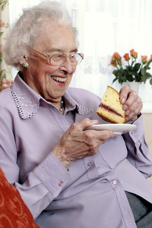 An old bespectacled woman sitting on the couch eating cake photo
