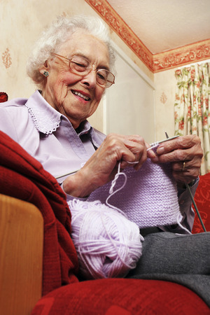 An old bespectacled lady sitting on the couch knitting photo