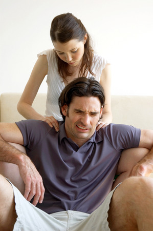 A man is in pain as his wife massaging his shoulder photo