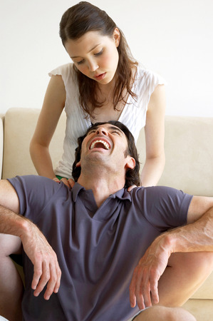 spoiling: A man laughing as his wife massaging his shoulder
