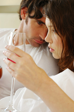 cuddled: A couple lying on the bed drinking wine Stock Photo