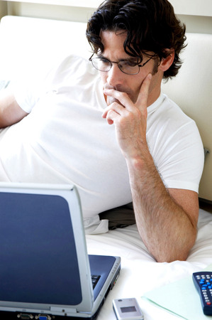 bespectacled man: A bespectacled man lying on the bed reading his work on the laptop