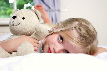 girl lying down: Una ni�a que se acuesta en la cama abrazando a un oso de peluche