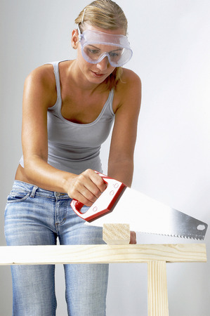 woodcraft: A woman with goggles sawing a wood