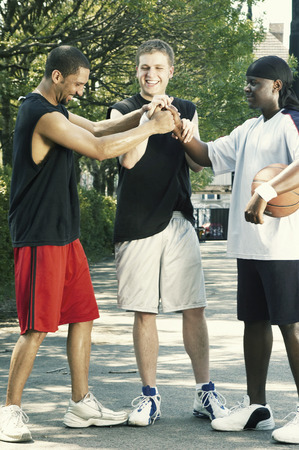 combined effort: Three basketball players grasping their hands in the middle