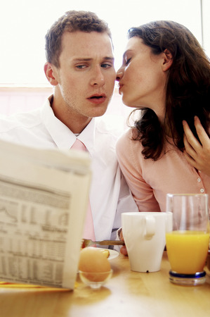 A man getting a kiss from his wife while having breakfast and reading newspaper photo
