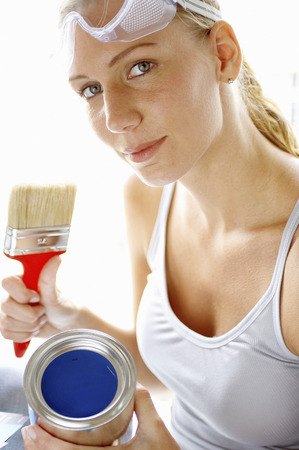 favorite colour: A woman with goggles holding a brush and a tin of blue paint Stock Photo