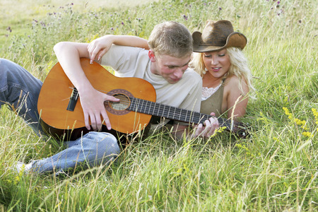 A guy playing a song on his guitar for his girlfriend photo