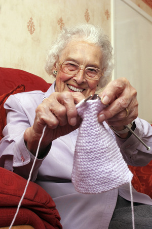 An old bespectacled lady sitting on the couch showing the camera how she knits photo