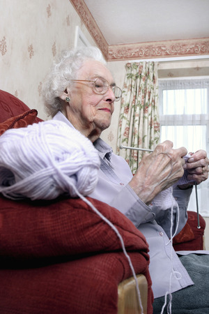 An old bespectacled woman sitting on the couch knitting photo